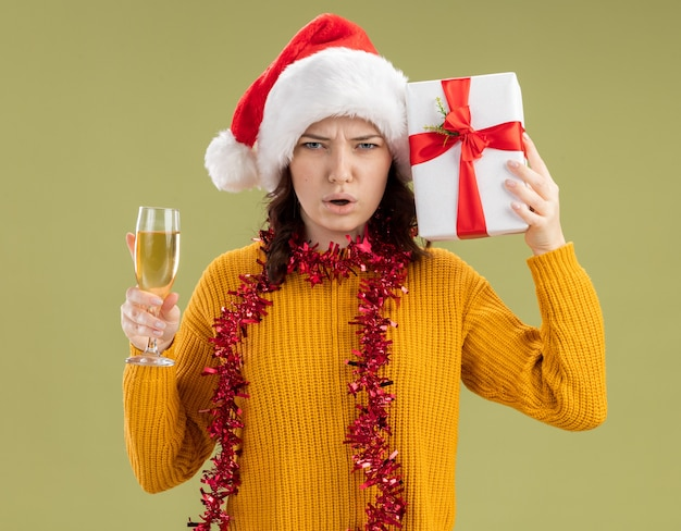 Unzufriedenes junges slawisches mädchen mit weihnachtsmütze und mit girlande um hals, die glas champagner und weihnachtsgeschenkbox lokalisiert auf olivgrünem hintergrund mit kopienraum hält