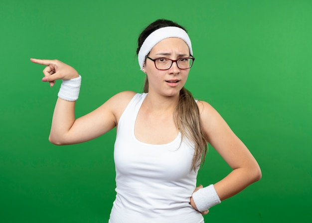 Unzufriedenes junges sportliches mädchen in optischer brille mit stirnband und armbändern zeigt an der seite