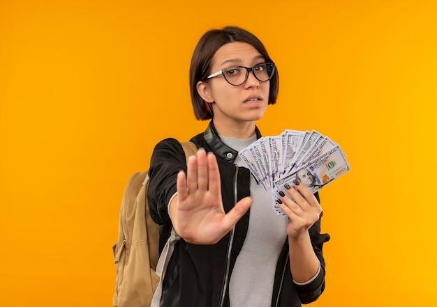 Unzufriedenes junges studentenmädchen, das brille und rückentasche hält, die geld gestikulieren stopp lokalisiert auf orange hintergrund mit kopienraum