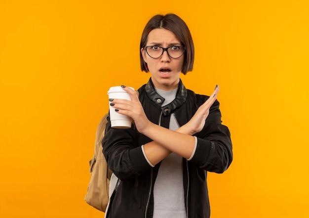 Unzufriedenes junges studentenmädchen, das brille und rückentasche hält, die kaffeetasse hält, die nicht lokalisiert auf orange hintergrund mit kopienraum gestikuliert