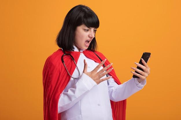Unzufriedenes junges superheldenmädchen, das stethoskop mit medizinischem gewand und umhang hält, der telefon an der orange wand isoliert hält und betrachtet