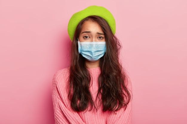 Unzufriedenes junges weibliches model trägt medizinische maske, ist schwer krank, kommt ins krankenhaus, um einen arzt aufzusuchen, hat eine virusinfektion, trägt grüne baskenmütze und pullover