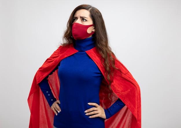 Unzufriedenes kaukasisches superheldenmädchen mit rotem umhang, das rote schutzmaske trägt