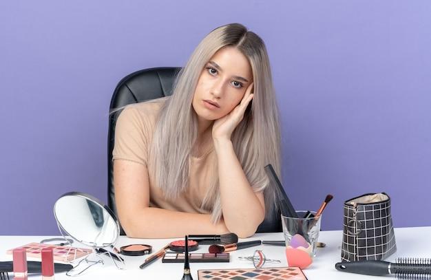 Unzufriedenes, kippendes junges, schönes mädchen sitzt am tisch mit make-up-tools und legt die hand auf die wange, isoliert auf blauem hintergrund