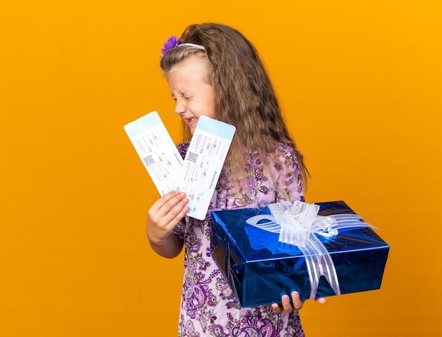 Unzufriedenes kleines blondes mädchen, das geschenkbox und flugtickets isoliert auf oranger wand mit kopierraum hält