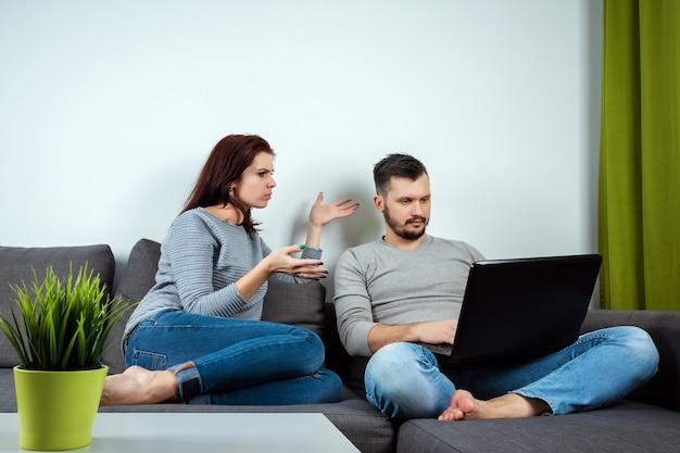 Unzufriedenes mädchen betrachtet einen kerl, der auf einem laptop spielt