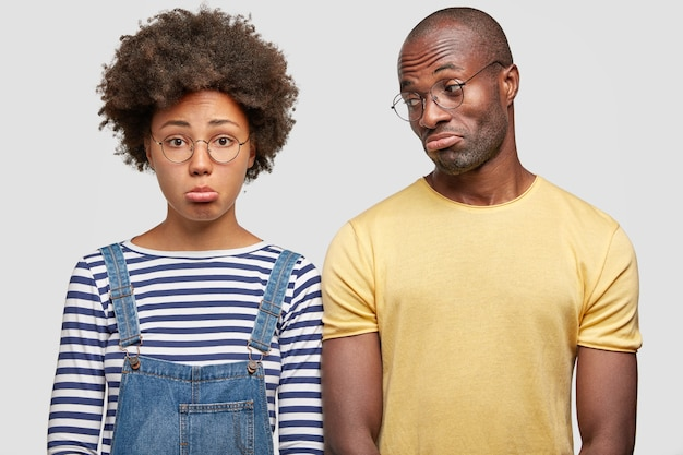 Unzufriedenes paar krümmt die unterlippen und sieht mit unglücklichen gesichtsausdrücken aus, als hätten sie den urlaub verdorben, lässig gekleidet