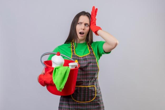 Unzufriedenes putzen junges mädchen in uniform in roten handschuhen mit reinigungswerkzeugen legte ihre hand auf den kopf auf isolierte weiße wand