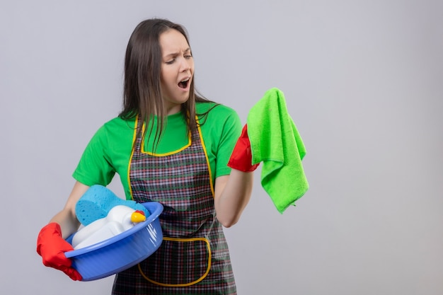 Unzufriedenes putzendes junges mädchen, das uniform in den roten handschuhen hält, die reinigungsjungen halten und auf ihrer hand auf isolierter weißer wand lappen suchen