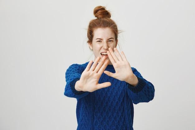 Unzufriedenes rothaariges mädchen, das nein sagt, stoppschild zeigt, gesicht mit ausgestreckten händen bedeckt