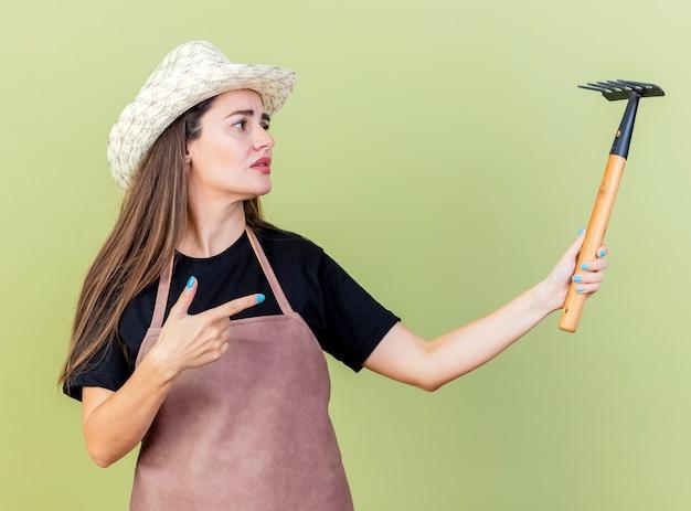 Unzufriedenes schönes gärtnermädchen in der uniform, die gartenhuthaltung hält und punkte auf rechen lokalisiert auf olivgrünem hintergrund