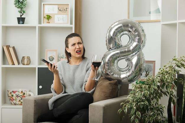 Unzufriedenes schönes mädchen an einem glücklichen frauentag, der ein glas wein mit dem telefon hält, das auf einem sessel im wohnzimmer sitzt