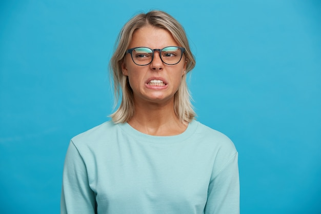 Unzufriedenes weibliches model runzelt das gesicht und beißt angewidert die zähne zusammen