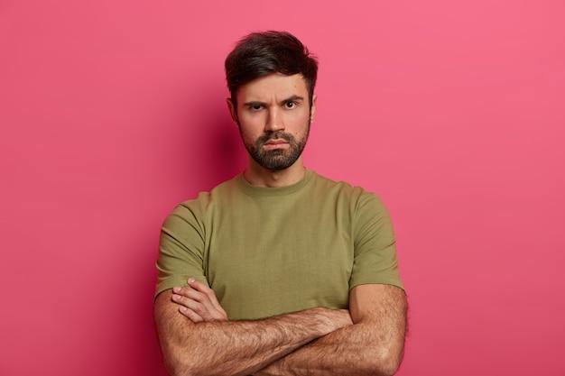 Unzufriedenheit unrasierter junger mann runzelt die stirn, sieht ernst und streng aus, hält die hände über dem körper gekreuzt, hört jemandem zu, wartet auf erklärungen, fordert trurth, trägt ein lässiges t-shirt