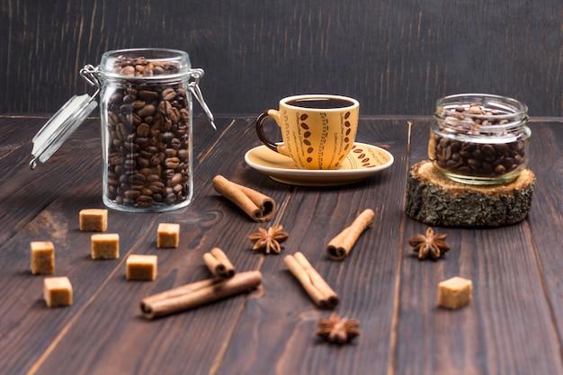 Up¡up kaffee, kaffeebohnen in gläsern. auf dem tisch zimtstangen