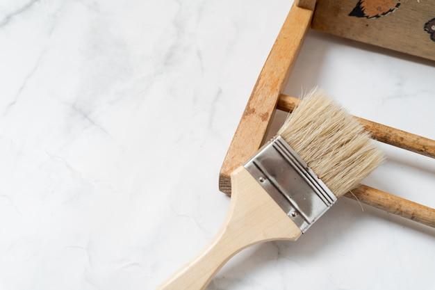 Upcycling-konzept. flach lag auf marmorhintergrund. mitte des jahrhunderts stuhl und werkzeuge. draufsicht