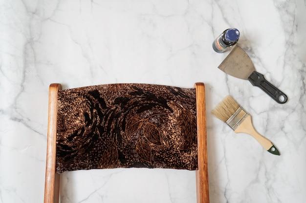 Upcycling-konzept. wohnung lag auf marmoroberfläche. mid century stuhl und werkzeuge. ansicht von oben