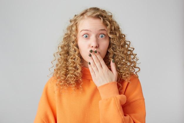 Ups, ich habe einen fehler gemacht! eine hübsche und attraktive blondine mit lockigen haaren steht in der kamera und bedeckt den mund mit der hand, als würde sie etwas besonderes sagen, das unangemessen ist und jemandes geheimnis gelüftet hat.