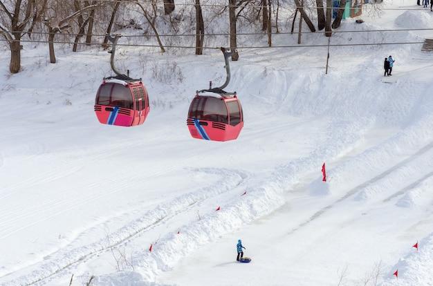 Ural-fluss im winter seilbahn und skifahren von einer eisrutsche im hain von zauralny