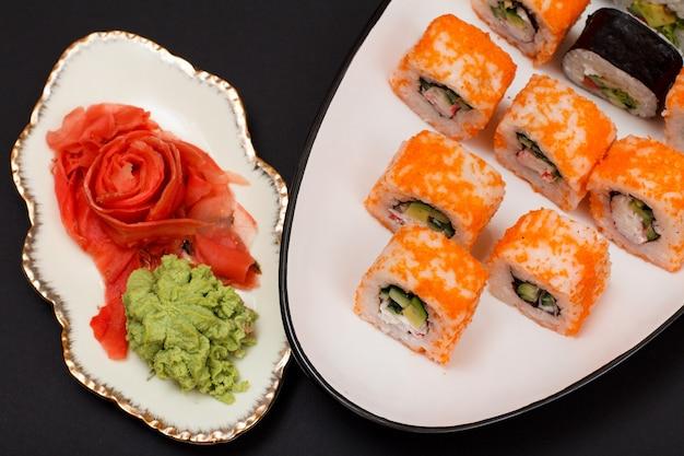 Uramaki kalifornien. sushi-rollen mit nori, reis, avocadostücken, gurken, dekoriert mit fliegendem fischrogen auf keramikplatte. teller mit rotem eingelegtem ingwer und wasabi. ansicht von oben. schwarzer hintergrund.