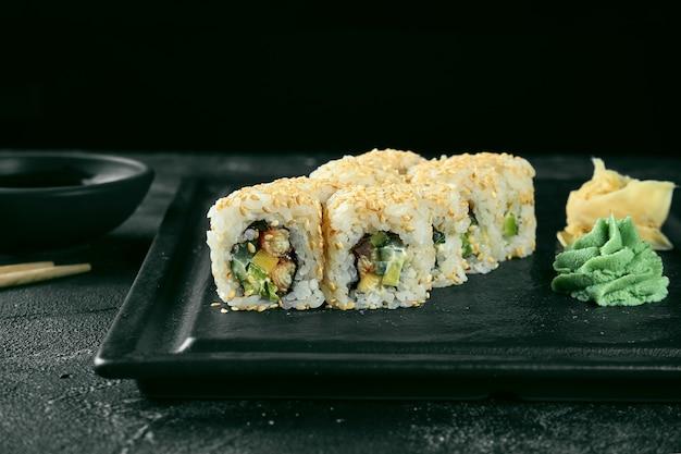 Uramaki sushi california roll in sesam mit aal, avocado und gurke. klassische japanische küche. lebensmittellieferservice.