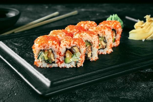 Uramaki sushi california roll in tobiko kaviar mit aal, avocado und gurke. klassische japanische küche. lebensmittellieferservice. getrennt auf weiß.