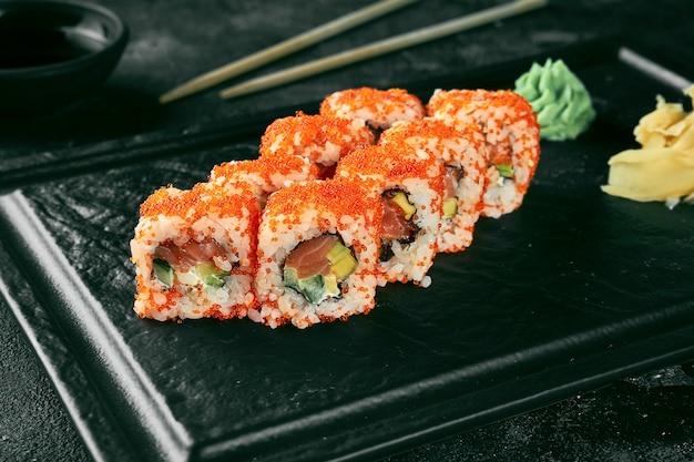 Uramaki sushi california roll in tobiko kaviar mit lachs, avocado und gurke. klassische japanische küche. lebensmittellieferservice.