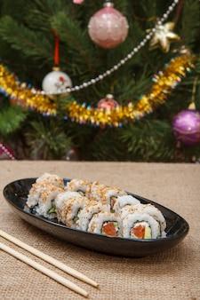 Uramaki-sushi-rollen mit avocado und rotem fisch auf keramikplatte, holzstäbchen auf sackleinen und weihnachtsbaum mit spielzeugbällen und girlanden im hintergrund.