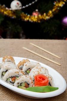 Uramaki-sushi-rollen mit rotem fisch und eingelegtem ingwer, avocadostück auf porzellanteller und holzstäbchen auf sackleinen. weihnachtsbaum mit spielzeugbällen und girlanden im hintergrund