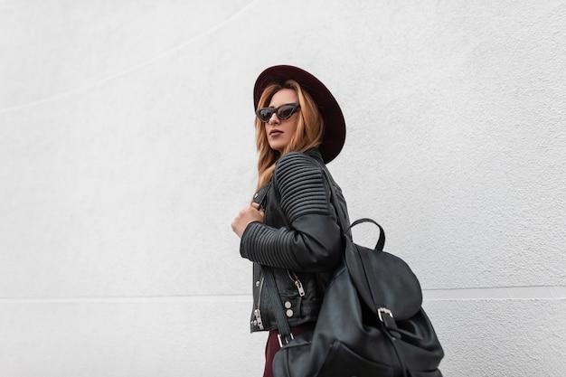 Urban hübsche junge hipster-frau in trendiger dunkler sonnenbrille in einem schicken hut in einer lederjacke mit einem schwarzen stilvollen rucksack