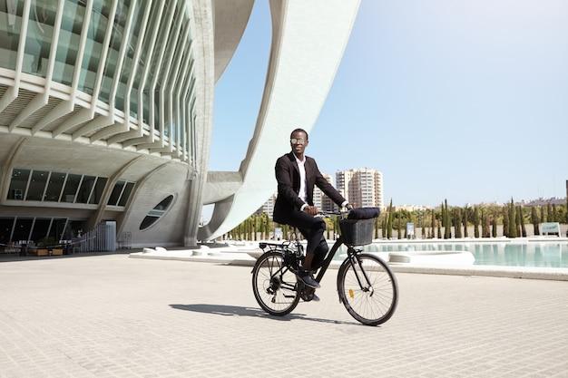 Urban lifestyle, ökologie und verkehrskonzept. modischer moderner umweltfreundlicher junger afroamerikanischer geschäftsmann, der trendige runde sonnenbrillen und formellen anzug trägt, der fahrrad fährt, um am fahrrad zu arbeiten