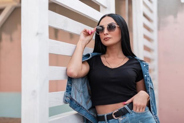 Urban stilvolle junge frau hipster in einem trendigen schwarzen top in einer modischen jeansjacke in einem rock in dunkler sonnenbrille posiert in der nähe einer weißen holzwand in der stadt. attraktives mädchenmodel im freien.