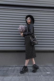 Urban woman brunette in elegantem hut mit sonnenbrille im schwarzen jugendkleid steht mit blumenstrauß lila blumen in der nähe von metall-vintage-wand im freien. stilvolles mädchen genießt spaziergang und frische schöne blumen.