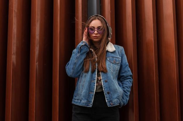 Urbane europäische junge hipster-frau in blauer jeansjacke der jugend in violetter modebrille steht in der nähe der roten, modernen, gestreiften metallwand in der stadt. attraktives mädchenmodell in modischer kleidung im freien. stil