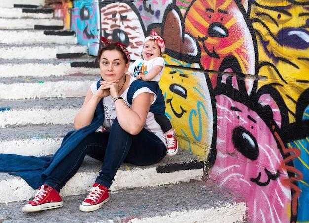 Urbaner lässiger familienlook und babytragen mit mama und kleinkindmädchen