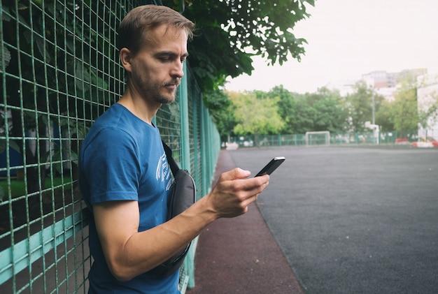 Urbaner lebensstil. junger bärtiger mann mit dem smartphone und umhängetasche, die nahe zaun des stadtsportspielplatzes bleiben.