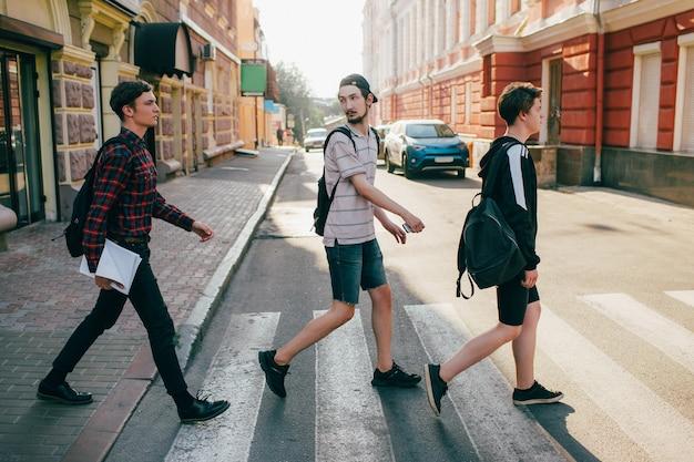 Urbaner teenager-hipster-straßenlebensstil. studenten gehen zum college oder gymnasium, um zu studieren. zebrastreifen-verkehrsgesetz-konzept