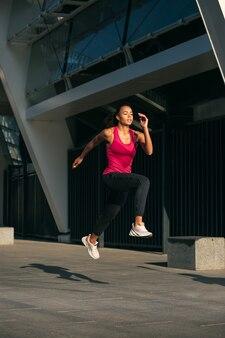 Urbanes foto mit einer sportlichen frau, die läuft und in der luft in bewegung ist