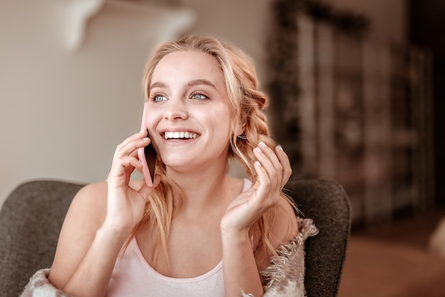 Urkomischer dialog. öffnen sie ansprechende frau mit breitem lächeln, das angenehmes chatten auf smartphone hat