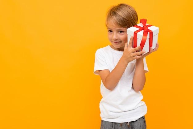 Urlaub . attraktiver junge mit geschenkbox auf hellem gelb