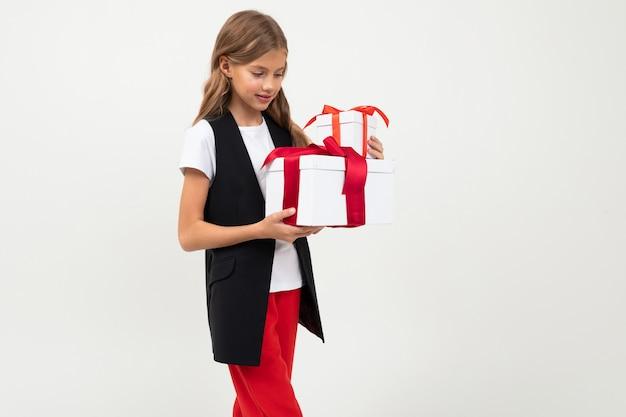 Urlaub . attraktives lächelndes mädchen mit einem geschenk mit einem roten farbband in ihren händen auf einem weiß mit copyspace