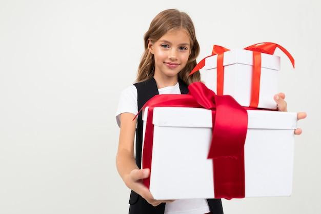 Urlaub . attraktives lächelndes mädchen mit einem großen geschenk mit einem roten band in ihren händen auf einem weiß