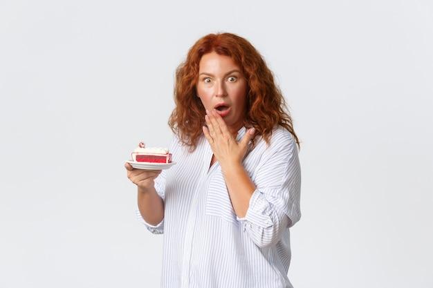 Urlaub, emotionen und lifestyle-konzept. schockierte und besorgte rothaarige frau mittleren alters mit offenem mund, die nach luft schnappt und besorgt aussieht, während sie kuchen hält, hört, wie viel kalorien sie hat.