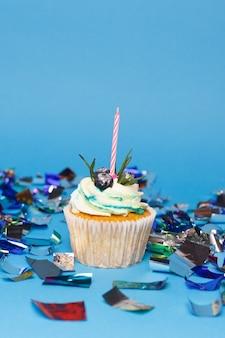 Urlaub, feier, gruß und partykonzept - geburtstagskuchen mit einer brennenden kerze auf blauem hintergrund, konfetti. konfetti für eine party.