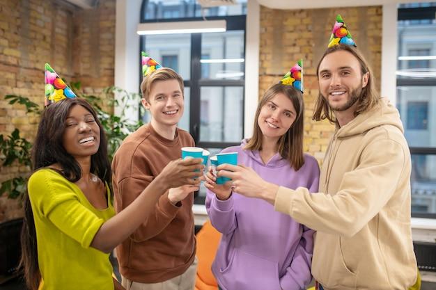 Urlaub, freunde. gruppe von fröhlichen jungen leuten in hellen partyhüten, die toast feiern ereignis machen