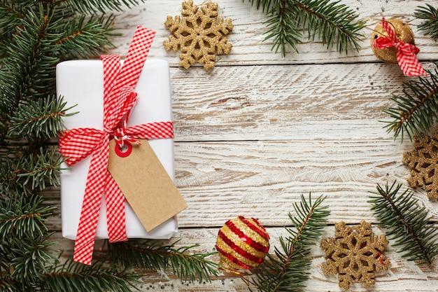 Urlaub geschenkbox. weihnachtsgeschenk mit tag am weißen hölzernen hintergrund.