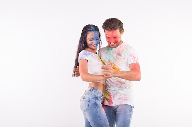 Urlaub, gesellschaftstanz, holi und menschen konzept - glückliches paar, das spaß hat und bachata oder kizomba mit mehrfarbigem puder auf ihren gesichtern auf weißer wand mit kopienraum tanzt