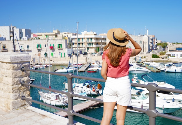 Urlaub in apulien. rückansicht des touristischen mädchens mit hut und blick auf den malerischen hafen von giovinazzo in apulien, italien.