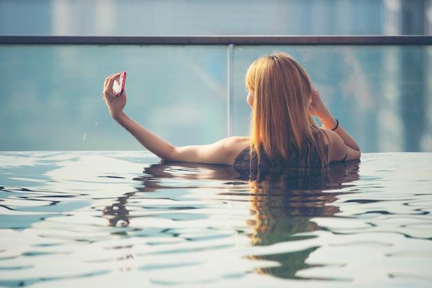 Urlaub in kuala-lumpur. junge frau genießen, im dachspitzenpool mit schöner stadtansicht zu schwimmen