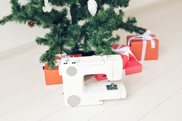 Urlaub, kleidungsdesign und geschenkkonzept - nähmaschine als geschenk unter dem weihnachtsbaum.